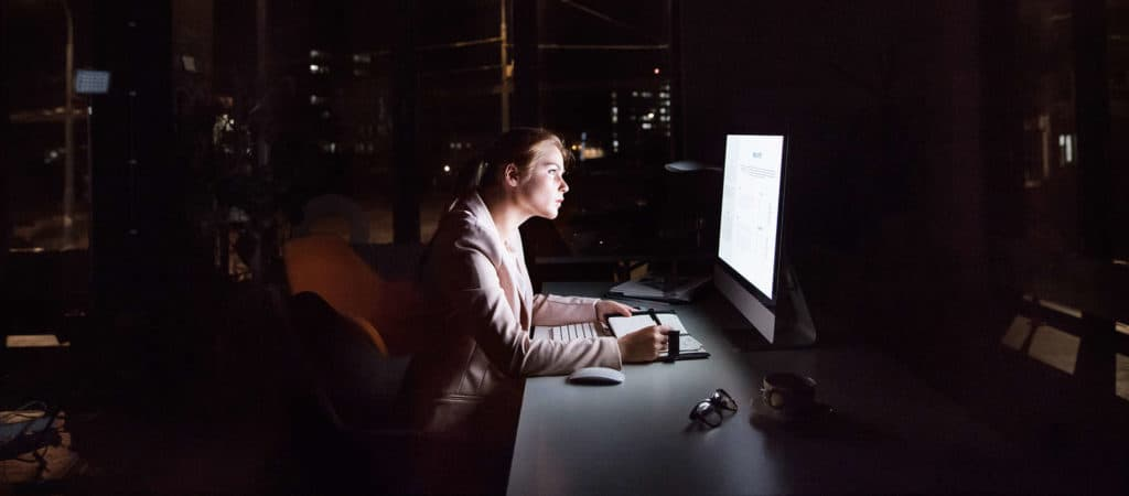 Businesswoman in front of computer screen in office at night