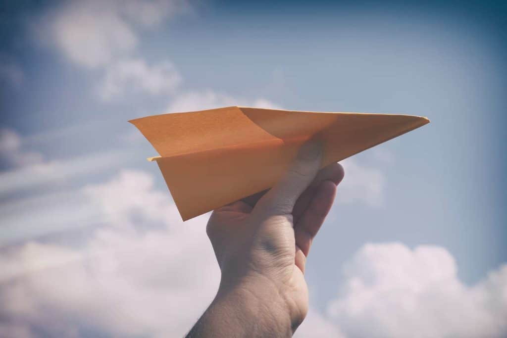 Paper plane in a hand against cloudy sky